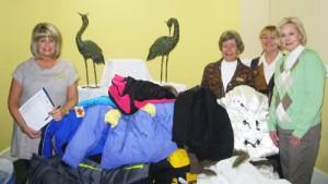 NMB Woman's Club members donate coats to local school children.